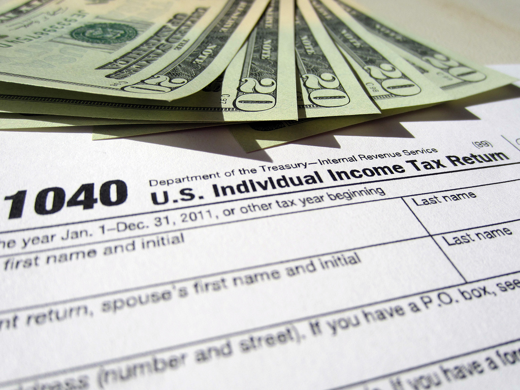1040 tax form with $100 in 20s above it