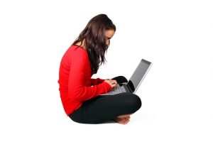 Woman sitting cross-legged with a laptop in her lap