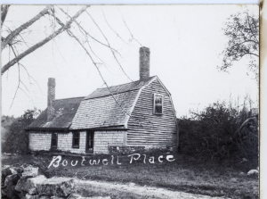 The Boutwell place with branches in the left top foreground and part of a stone wall in the bottom left foreground. Dense bushes behind the house.