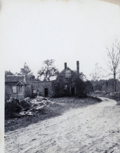 The Boutwell palce with a disorganized pile of wooden planks in front of the house to the left.