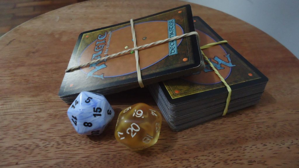 Two decks of Magic: The Gathering, with one deck forming a ramp on top of the other and two dice, one white with black lettering and one gold with white lettering in from of the ramp-desk