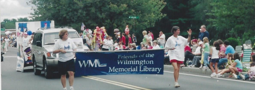Two members of The Friends of the Wilmington Memorial Library with their banner between them marching in a parade.