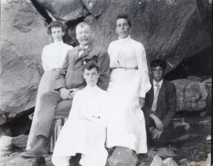 Mattie Nichols Eames Standing to the right of a seated Ed Nelson Eames with a kneeling Harold Eames with an unknown women between the two men and an unknown women seated in front of Ed. Big Rocks behidn them all.