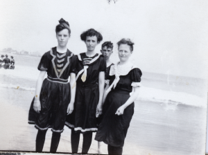 Three girls and a guy at a beach. The second from the left is Mattie Nichols.