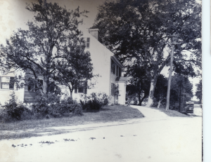 Gowing Swain's house from across the street with a tree in front and left of it and a taller tree behind right.