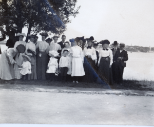Group of people, with Walter Rollins in the middle back, in front of a lake with a tree to the rear left of the picture. Circa 1903