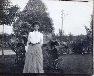Mattie Nichols Eames standing in front of some trees with a streetcar pole in the background