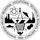 """A circle with the words (starting at the bottom of the circle with the bottom of the words towards the inner part of the circle) """"Shawsheen Valley Regional Vocational Technical School District 1965"""" In that circle is an open book in front of a compass, protractor and with a slide rule going through the middle. Directly below those two is an engine with a car to the left and a set of interlocking gears to the right. Above all that is a diagram of an atom. In the background is a skyline with smoke coming out of the stacks on the right and an old-fashioned antenna on the left."""