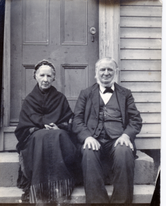 Mr. and Mrs. Henry Sheldon sitting on steps in front of a house.