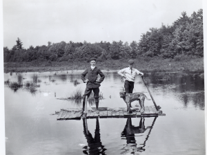 Harold Eames and Robert Carter standing on a raft in the water with a dog. Trees in the background.