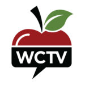 The top part of a red apple, with black stem and green leaf, above a black square speach bubble with the white letters WCTV inside.